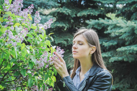 woman with long hair on lilac flowers Imagens