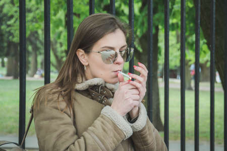 Closeup fashion woman portrait of young pretty fashionable girl in sunglasess, street fashion on a park bench by smoking cigarettes Imagens