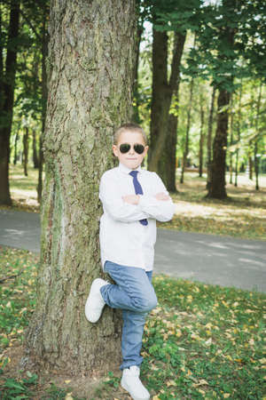 Portrait of a handsome eight year old boy in sunglasses outdoors 版權商用圖片