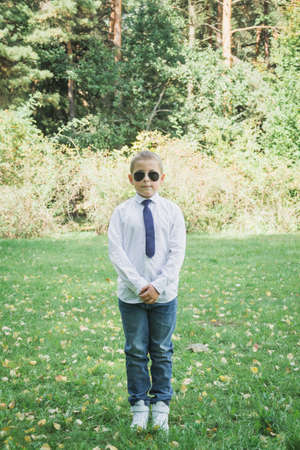 Outdoor Portrait of a handsome eight year old boy in sunglasses Stock Photo