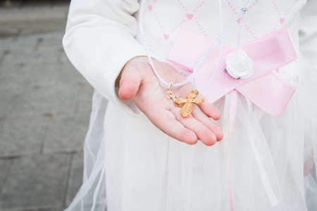 Two small Orthodox crosses in the hands of a small child after the baptismal rite in the church