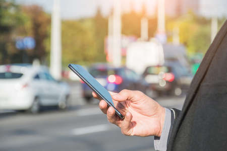Taxi search or transport, business trip, technology and people concept - close up of young man hand with smartphone on city car road background Stock Photo