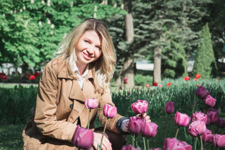 portrait of a beautiful blonde woman and tulips on a summer day
