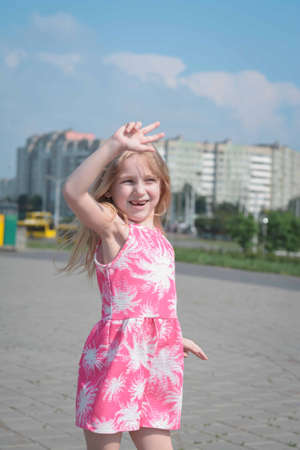 cheerful portrait of a little five year old girl in a pink summer dress on the streets of her city on a summer day
