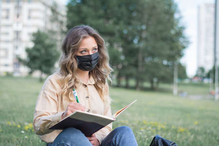 Student wearing a mask studying on a campus lawn