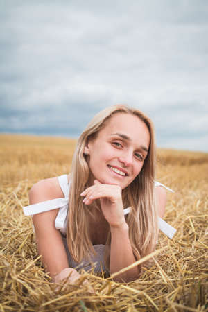 Portrait of bohemian girl with white art posing over wheat field a summer day