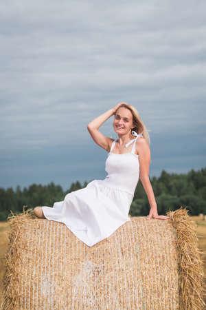 Happy woman enjoying life in golden wheat field, summer time 免版税图像