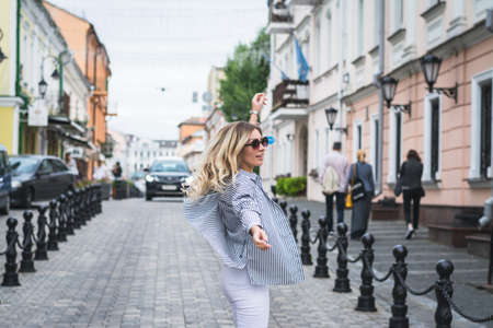 happy stylish girl waving her arms and spinning on the street of her city