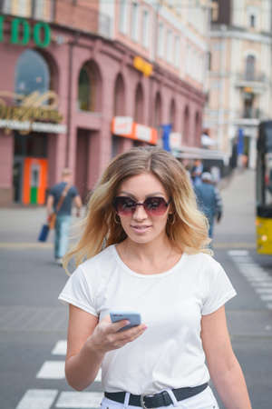 Young cheerful stylish woman using cell phone and texting message on city street