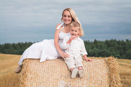 Happy family mom and son in a summer wheat field