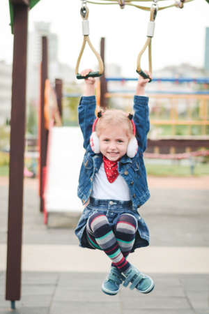 beautiful little girl playing in the playground outdoor