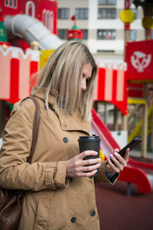Beautiful woman with coffee cup in the street typing a message on her phone 免版税图像