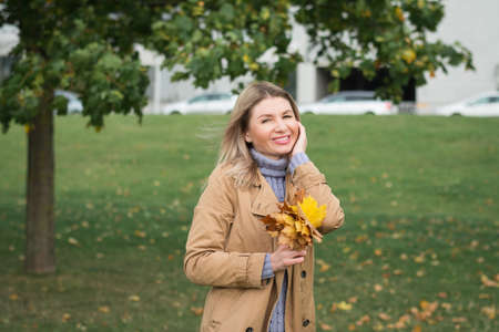 Beautiful woman portrait in autumn park with a bouquet of fallen leaves