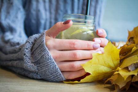 female hands close and hot fruit tea