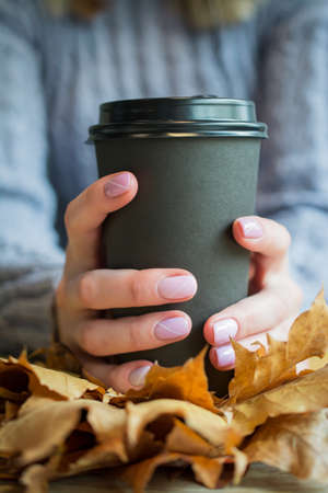 Big cup of coffee and female hands with beautiful nails