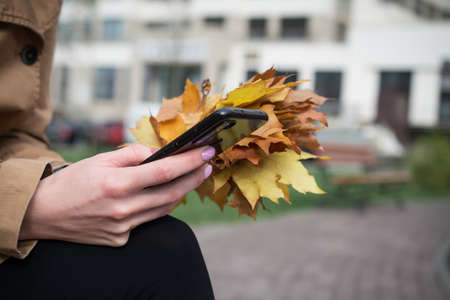 Close-up of female hands pointing finger on screen smart phone outdoor