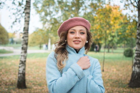 Beautiful girl in a blue coat and beret in an autumn park