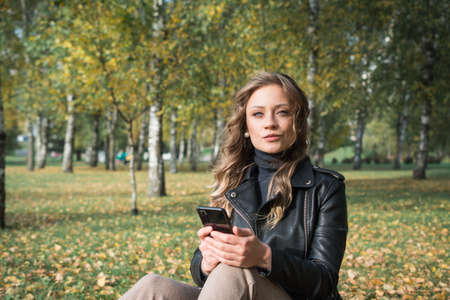 Beautiful young woman in black leather jacket in autumn park 免版税图像