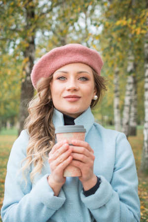 Young woman with coffee cup autumn outdoor