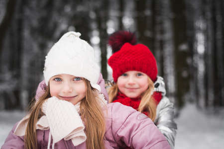 Two beautiful little girls sisters are playing in the winter park