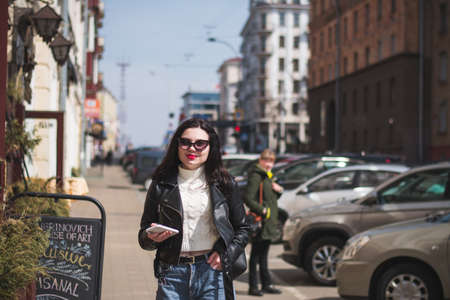 Beautiful young girl student hipster walks along the street of her city