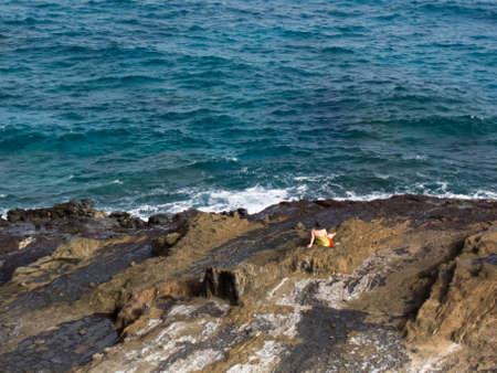 gazing: Rocky Surf on Oahu Coastline and Woman Gazing Stock Photo