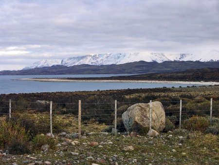 mesmerized: Patagonian landscape with fence and lake near torres del paine Stock Photo