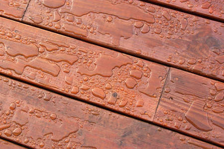 hydrophobic: Pooled water on finished deck with wood grain