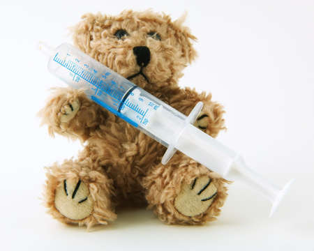 Teddy bear holding a syringe used to measure medication on a white background