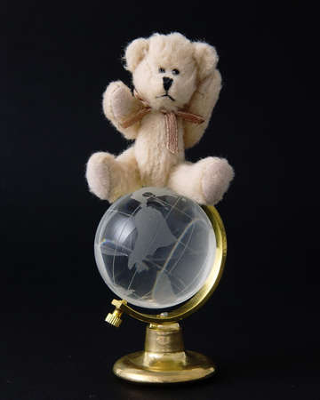 Teddy bear on top of the world isolated on a black background