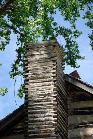 An old log cabin chimney on a spring day