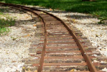 curving: Rusty train tracks curving around a bend