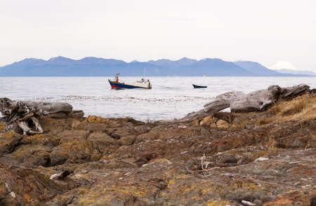 Fishing boat towing a skif in the straits of Magellan