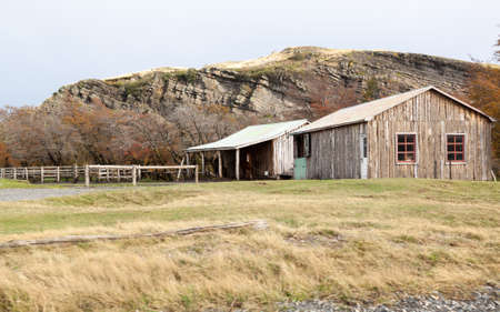 Patagonian ranch made with logs and a horse under an awning