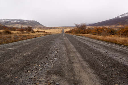 Dirt road vanishing into the distance down a hill