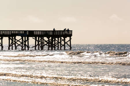 Silhouette of Men fishing on a pier with sunlight glinting off of the wavelets photo