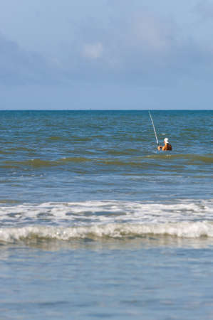Waves on a sandy beack in Isle of Palms with a fisherman in the distance
