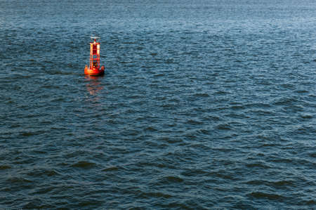 Bright red maritime buoy in the middle of the ocean, surrounded by blue water. photo