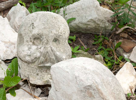 Stone skull in Mayan style lying on the ground at Xcaret,