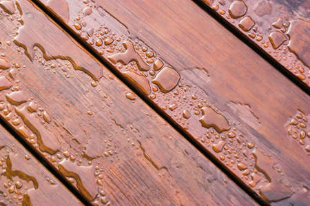 Pooled water on finished deck with woodgrain. Excellent background for illustrating construction or resilience.