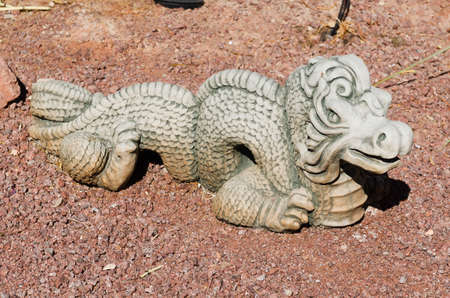 Ornamental dragon statue in a stone garden surrounded by red rock Stock Photo