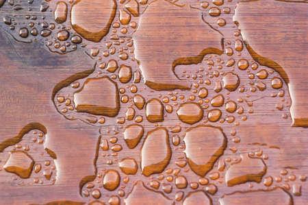 Agua acumulada en la cubierta acabada con vetas de la madera. Excelente fondo para ilustrar la construcción o la resiliencia. Foto de archivo - 20703346