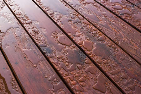 hydrophobic: Pooled water on finished deck with woodgrain. Excellent background for illustrating construction or resilience.
