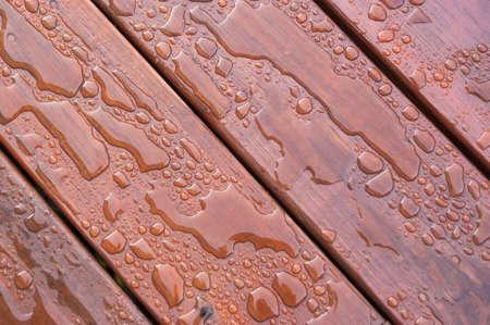 Agua acumulada en la cubierta acabada con vetas de la madera. Excelente fondo para ilustrar la construcción o la resiliencia. Foto de archivo - 20703352