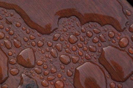 Agua acumulada en la cubierta acabada con vetas de la madera. Excelente fondo para ilustrar la construcción o la resiliencia. Foto de archivo - 20703355