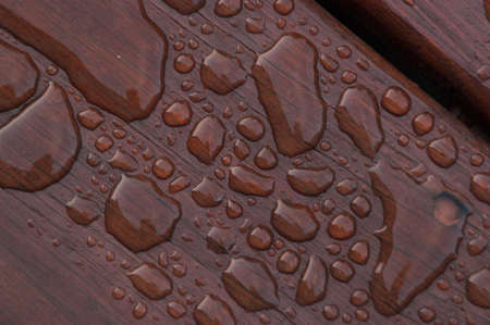 Agua acumulada en la cubierta acabada con vetas de la madera. Excelente fondo para ilustrar la construcción o la resiliencia. Foto de archivo - 20703356