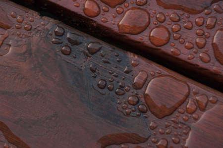Agua acumulada en la cubierta acabada con vetas de la madera. Excelente fondo para ilustrar la construcción o la resiliencia. Foto de archivo - 20703364