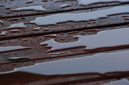 Agua acumulada en la cubierta acabada con vetas de la madera. Excelente fondo para ilustrar la construcción o la resiliencia. Foto de archivo - 20703366