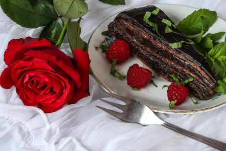 chocolate cake with raspberries and red rose