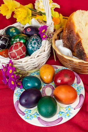 Easter eggs and Easter bun with flowers - red background Stock Photo
